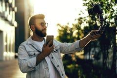 El blogger masculino barbudo del inconformista en los vidrios de moda que se colocan en la calle de la ciudad, sostiene la cámara imagen de archivo