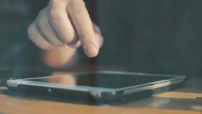 El blogger mecanografía el texto en la tableta en el café almacen de metraje de vídeo