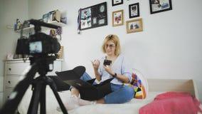 El blogger popular de la muchacha bonita está registrando el vídeo sobre la caja de apertura con los cosméticos almacen de video