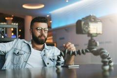 El blogger video masculino barbudo crea el contenido video para su canal El vlogger del hombre se alivia en cámara con el trípode fotos de archivo