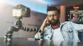 El blogger video masculino barbudo joven crea el contenido video para su canal El individuo feliz tira el vídeo que fluye para lo fotos de archivo libres de regalías