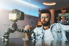 El blogger video masculino barbudo joven crea el contenido video para su canal El individuo feliz tira el vídeo que fluye para lo imágenes de archivo libres de regalías