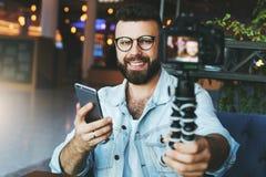 El blogger video masculino barbudo joven crea el contenido video para su canal El individuo feliz tira el vídeo que fluye para lo fotografía de archivo libre de regalías