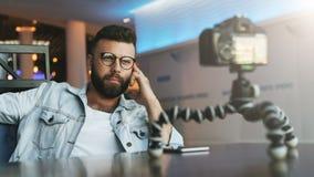 El blogger video masculino barbudo joven crea el contenido video para su canal El individuo feliz tira el vídeo que fluye para lo imagen de archivo libre de regalías