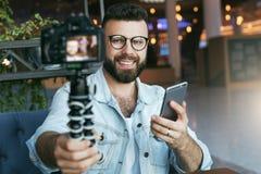 El blogger video masculino barbudo joven crea el contenido video para su canal El individuo feliz tira el vídeo que fluye para lo imagenes de archivo