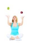 El blonde agradable hace juegos malabares manzanas Imagenes de archivo