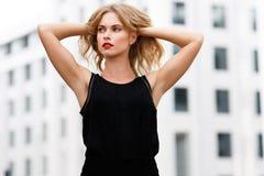 El blonde atractivo en pelo negro de la blusa aumenta sus manos imágenes de archivo libres de regalías