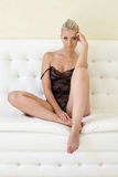 El blonde atractivo se vistió en la bata de casa que presentaba en el sofá Imagenes de archivo