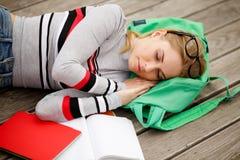 El Blonde con los vidrios y los libros de texto está durmiendo Foto de archivo libre de regalías