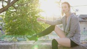 El blonde de la mujer de moda se sienta en la calle en la puesta del sol metrajes