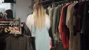 El blonde de moda está caminando en un pasillo comercial de la tienda cerca se coloca con ropa almacen de metraje de vídeo