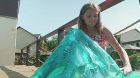 El blonde de pelo largo joven sopla para arriba el colchón por la piscina metrajes