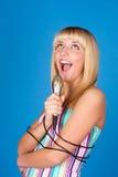 El blonde dulce canta en un micrófono Imagenes de archivo