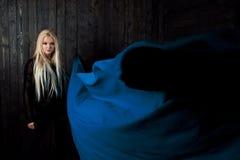 El blonde elegante en un fondo oscuro con la tela brillante del vuelo, colorea el azul Foto de archivo