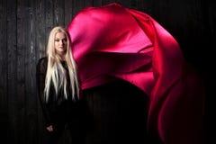 El blonde elegante en un fondo oscuro con la tela brillante del vuelo, colorea rosa Foto de archivo libre de regalías