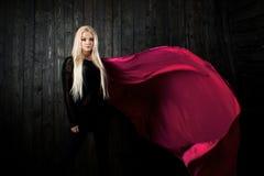 El blonde elegante en un fondo oscuro con la tela brillante del vuelo, colorea rosa Fotografía de archivo