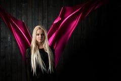 El blonde elegante en un fondo oscuro con la tela brillante del vuelo, colorea rosa Imágenes de archivo libres de regalías