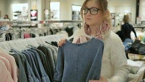 El blonde elegante que elige los pedazos básicos de ropa para el guardarropa, opción de la ropa para mujer en la tienda, muchacha almacen de video