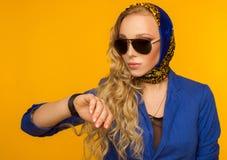 El Blonde en un pañuelo azul y una chaqueta en gafas de sol mira el th Imagen de archivo