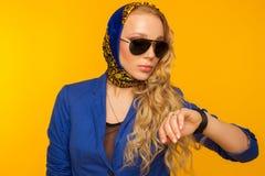 El Blonde en un pañuelo azul y una chaqueta en gafas de sol mira el th foto de archivo