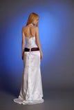 El Blonde en un vestido de noche blanco elegante se coloca con el suyo detrás dado vuelta en perfil Fotos de archivo