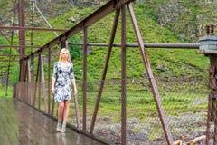 El Blonde en vestido corto del color, las piernas largas en zapatos camina en un bridg imagenes de archivo