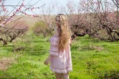 El Blonde en vestido rosado camina en el jardín con los árboles florecientes Fotografía de archivo libre de regalías