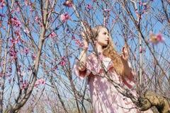 El Blonde en vestido rosado camina en el jardín con los árboles florecientes fotografía de archivo