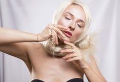 El blonde hermoso con el pelo largo que llora, soportando sus manos Imagen de archivo libre de regalías