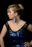 El blonde hermoso con el pelo rizado en un vestido azul con la lentejuela Foto de archivo