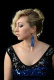 El blonde hermoso con el pelo rizado en un vestido azul con las lentejuelas, con los pendientes azules en un fondo negro Cara en  Fotografía de archivo