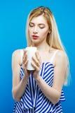 El Blonde hermoso con los hombros desnudos que llevan el vestido rayado está llevando a cabo la vela blanca en sus manos y está m Foto de archivo