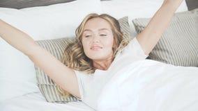 El blonde hermoso en su cama la abre los ojos, despierta y estira almacen de video