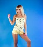 El blonde hermoso en un amarillo se divierte la ropa Fotografía de archivo
