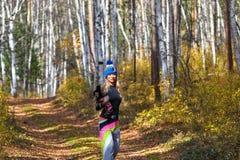 El blonde hermoso en un casquillo hecho punto camina con el perro en la madera del otoño Imagen de archivo libre de regalías