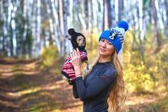 El blonde hermoso en un casquillo hecho punto camina con el perro en la madera del otoño Imagenes de archivo
