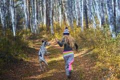 El blonde hermoso en un casquillo hecho punto camina con el perro en la madera del otoño Foto de archivo