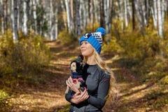 El blonde hermoso en un casquillo hecho punto camina con el perro en la madera del otoño Fotografía de archivo