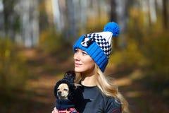 El blonde hermoso en un casquillo hecho punto camina con el perro en la madera del otoño Fotos de archivo
