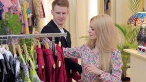 El blonde hermoso joven con su novio elige el vestido en tienda de ropa almacen de metraje de vídeo