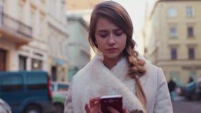 El blonde hermoso joven está mandando un SMS en su teléfono mientras que camina abajo de la calle Ella parece decepcionada de lo  almacen de video