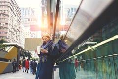 El blonde hermoso joven está viajando por el exterior derecho del trabajo usando la conexión libre del wifi fotografía de archivo libre de regalías