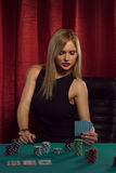 El blonde hermoso joven mira sus tarjetas imagen de archivo