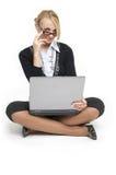 El blonde hermoso se sienta con la computadora portátil. Fotos de archivo