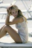El blonde hermoso se sienta en una silla de cubierta en la playa Foto de archivo