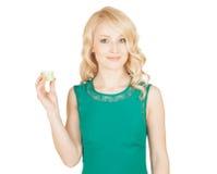 El blonde hermoso sostiene un tarro poner crema en una mano Imagen de archivo