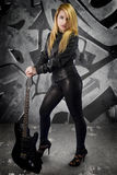 El blonde joven atractivo se vistió en cuero negro con la guitarra eléctrica Imagen de archivo