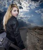 El blonde joven atractivo se vistió en cuero negro con la guitarra eléctrica Fotos de archivo libres de regalías