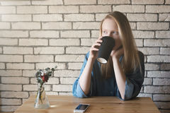 El blonde joven en camisa azul se sienta en la tabla en un café en el cual Fotos de archivo