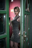 El blonde joven encantador con cortocircuito de la plata cupo firmemente el vestido que presentaba en un marco de puerta pintado  foto de archivo